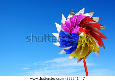 Colorful windmill toy against blue background - stock photo