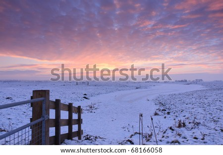 Colorful winter sunset in the Dutch countryside. - stock photo