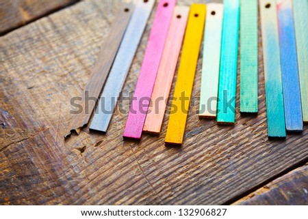 Colorful wood stain color test samples, on rough wood. - stock photo