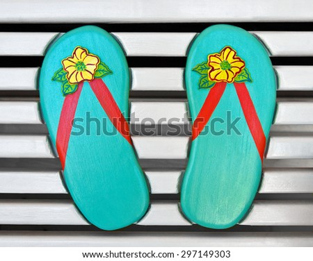 Colorful Wooden Flip-Flips on the back of a White Wood Bench  - stock photo