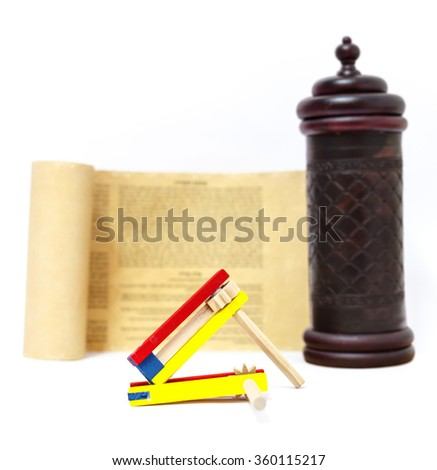 Colorful wooden noisemaker with Megillah Purim holiday background - stock photo