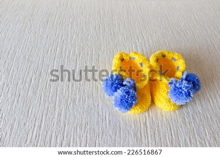 Colorful wool baby shoes on white background - stock photo
