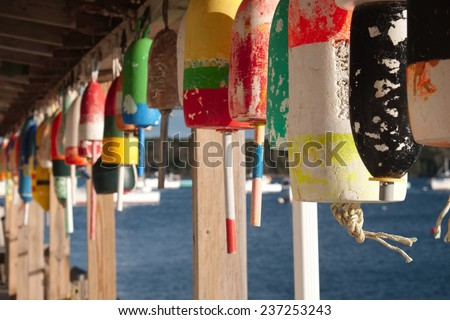 Colorful working boat lobster floatS hanging on the deck of a lobster processing plant with lobster boats in the background on a perfect autumn day - stock photo