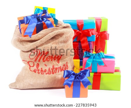 Colorful Xmas background with Santas gift sack filled to overflowing with multicolored gift-wrapped Christmas boxes and presents tied with ornamental bows over white - stock photo