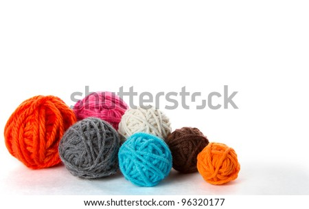 Colorful yarn balls in assorted sizes on a white background - stock photo