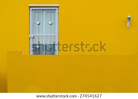 Colorful yellow home facade in the historic Bo-Kaap neighborhood in Cape Town.  The area is also known as the Malay Quarter, known for its colorful homes. - stock photo