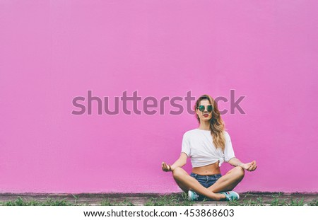Colorful yoga. Attractive young woman sitting on lotus position on the ground against pink wall. - stock photo