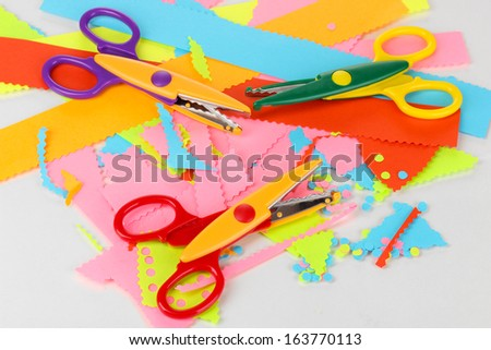 Colorful zigzag scissors on color paper close-up isolated on white - stock photo