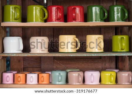 Colorful zinc cup on wooden shelves - stock photo