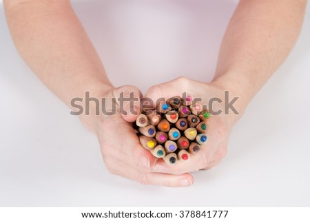 coloring pencils bunch in hands shot on a white background top view - stock photo