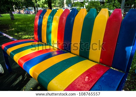 Colorized plastic bench in a park after rain - stock photo