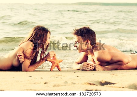 Colorized vintage outdoor portrait of  beautiful romantic couple of topless girl and muscular guy in jeans laying face to face with asteroid on beach - stock photo