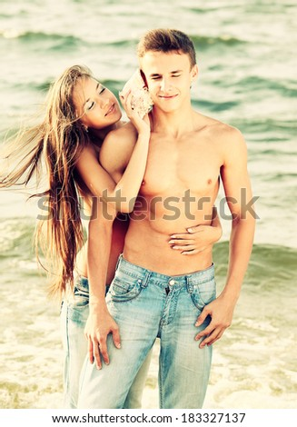 Colorized vintage outdoor portrait of beautiful topless girl putting shell to muscular guy's ear - stock photo