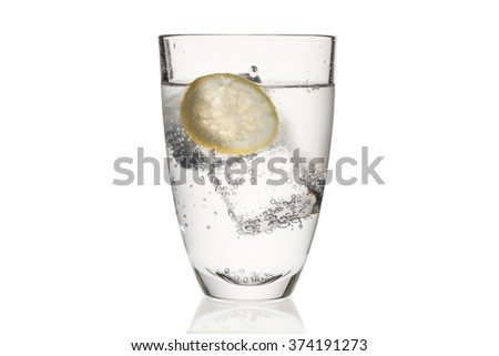 colorless bubbled tonic with a yellow lemon slice and transparent ice cubes in  a crystal glass - stock photo