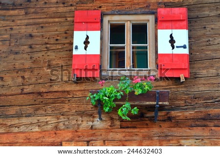 Colors of the Austrian flag on the shutters of traditional house in Tirol, Austria - stock photo