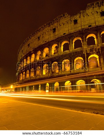 Colosseum and traffic lights at night in Rome, Italy - stock photo