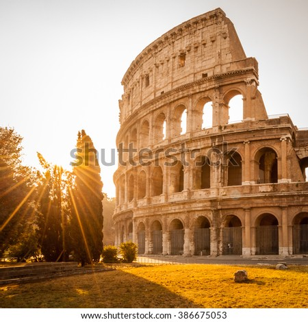 Colosseum at sunrise with sunstars, Rome, Italy - stock photo