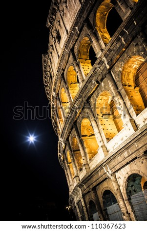 Colosseum (Rome) in a summer night with the moon - stock photo