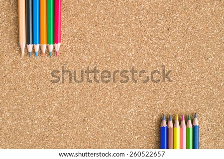 Colour pencils on cork board background close up - stock photo