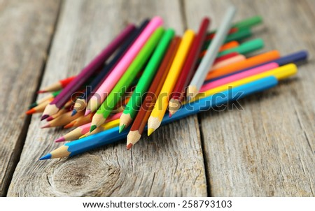 Colour pencils on grey wooden background - stock photo