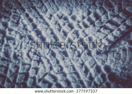 Colour picture of tire tracks in snow - stock photo