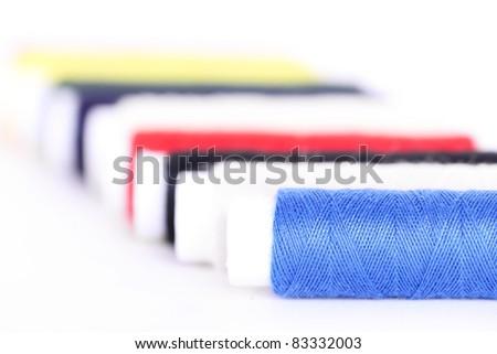 Colour threads bobbins, closeup on white - stock photo