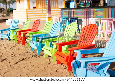 Coloured beach chairs. Sand beach. Multicolored lounge chairs. Summer Holiday vacation itinerary. - stock photo