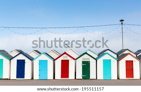 Colourful beach huts with blue red and green doors in a row - stock photo
