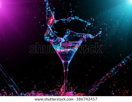 Colourful cocktail in glass with splash on the dark background - stock photo