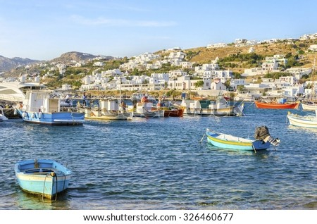 Colourful fishing and sail boats anchored on the Chora port in Mykonos, Greece. A view of a typical greek island harbour, whitewashed buildings on the hill and blue sea on a sunny day - stock photo