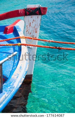 colourful fishing boat in turquoise waters - stock photo