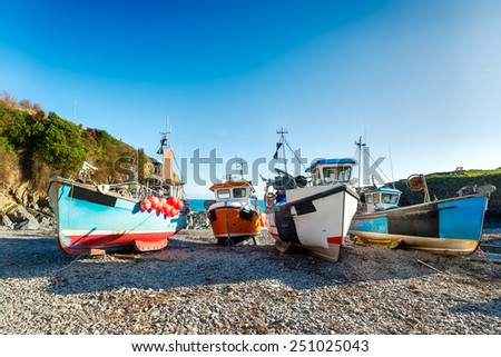 Colourful fishing boats on the beach at Cadgwith on the Lizard in Cornwall - stock photo