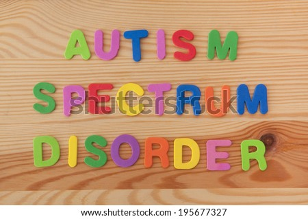 Colourful foam letters spelling out Autism spectrum disorder on a wooden background - stock photo