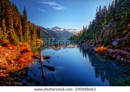 Colourful foliage along lake and distant mountains - stock photo