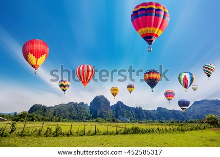 Colourful hot-air balloons flying over the mountain. - stock photo