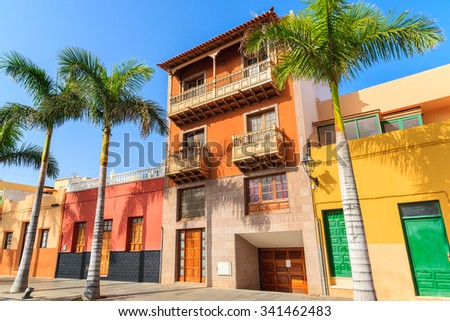 Colourful houses and palm trees on street in Puerto de la Cruz town, Tenerife, Canary Islands, Spain - stock photo