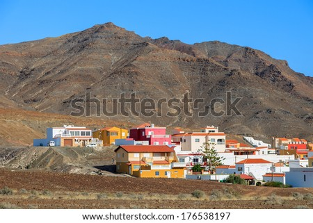 Colourful houses and volcano mountain in the background near Las Playitas town, Fuerteventura, Canary Islands, Spain - stock photo