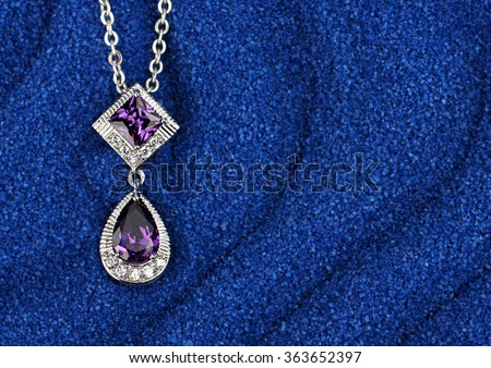 colourful Jewelry pendant with gems on blue sand waves background - stock photo