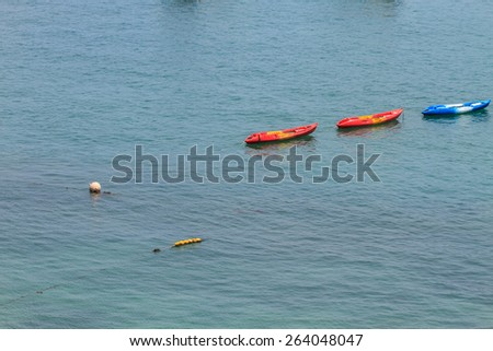 Colourful kayaks floating on tropical sea - stock photo