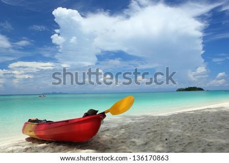 Colourful kayaks on tropical beach - stock photo