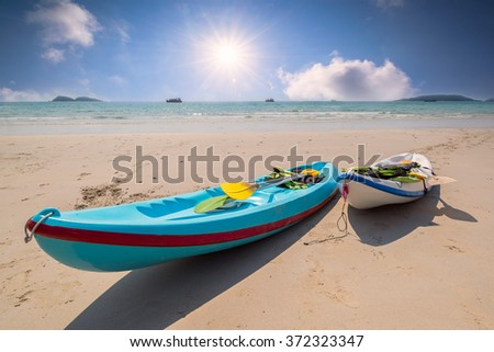 Colourful kayaks on tropical beach. - stock photo