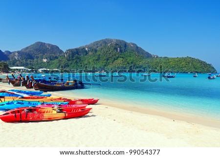 Colourful kayaks on tropical beach. - stock photo