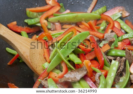 Colourful meat and vegetable stir-fry being cooked in black wok - stock photo
