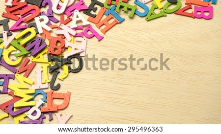 Colourful mix of wooden alphabet letters on table with wooden surface. Concept of message notice board and education. Slightly defocused and close-up shot. Copy space. - stock photo