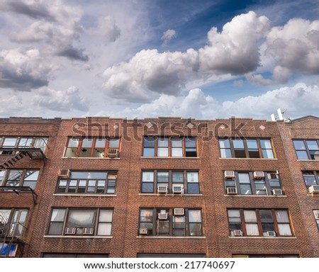 Colourful New York building with external fire escape ladders. - stock photo