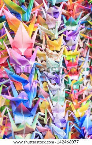 Colourful paper birds hanging together using fishing lines. Shallow depth of field. - stock photo