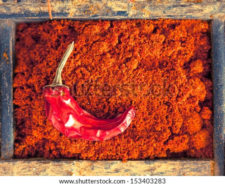 Colourful red chilli powder with a dried cayenne chilli pepper, a strong pungent spice with a hot flavour used as a seasoning and flavouring in cookery - stock photo