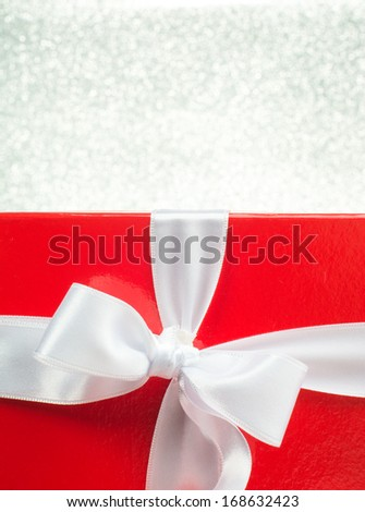 Colourful red Christmas gift decorated with a red ribbon - stock photo