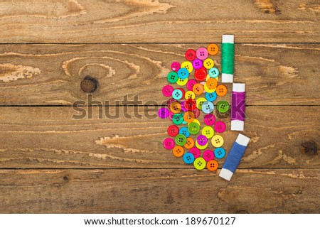 Colourful sewing buttons and rolls of thread on a wooden background with copy space.  - stock photo
