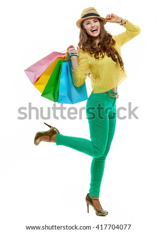 Colourful shopping vibes. Full length portraits of cheerful brunette woman in hat and bright clothes with shopping bags - stock photo